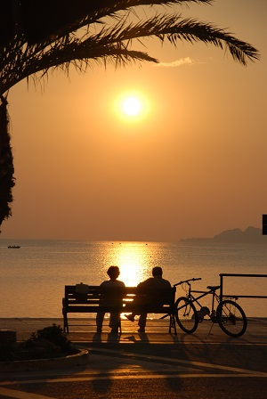 Pareja en banco viendo puesta de sol